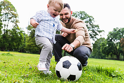 Happy father playing football with son in a park - p300m1587953 by Uwe Umstätter