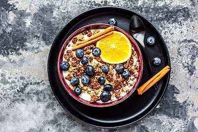 Crunchy muesli with blueberries, slice of orange and cinnamon sticks - p300m2070812 by Sandra Roesch