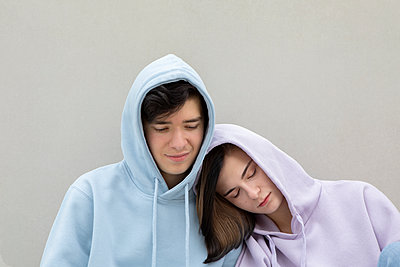 Teenage couple in hooded shirt by gray wall - p300m2276302 by Petra Stockhausen