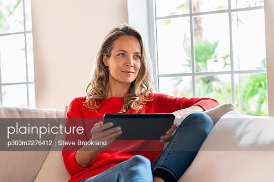 Smiling woman relaxing while holding digital tablet on couch in living room - p300m2276412 by Steve Brookland