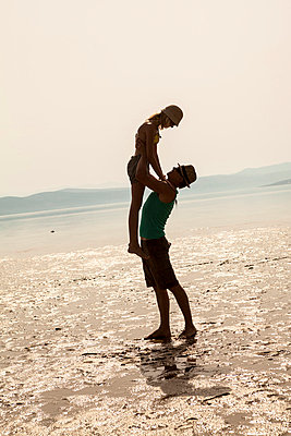 Croatia, Young couple on beach fooling about - p1026m762665f by Dario Secen