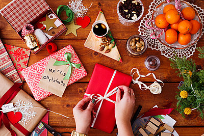 Directly above shot of hands tying ribbon on Christmas gift at wooden table - p1264m1122154f by Astrakan