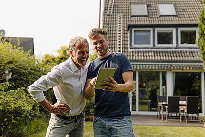 Son showing digital tablet to father in back yard - p300m2274999 by Gustafsson