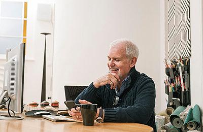 Senior man smiling, using mobile phone at work desk - p429m1206879 by Colin Hawkins