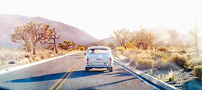 Vintage car driving on desert road - p555m1410786 by Emily Suzanne McDonald