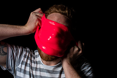 Man covering his face with red slime - p851m2205870 by Lohfink