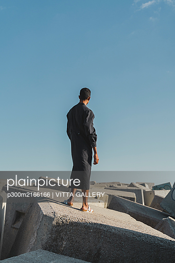 Young man wearing black kaftan standing on concrete blocks under blue sky - p300m2166166 by VITTA GALLERY
