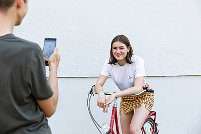 Boyfriend taking photo of his girlfriend on bicycle - p294m2132938 by Paolo
