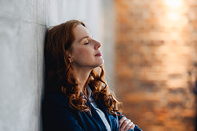 Redheaded businesswoman having a break leaning against a wall in office - p300m2140815 by Kniel Synnatzschke