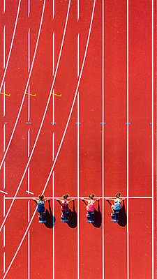 Germany, Baden-Wurttemberg, Winterbach, Aerial view of female sprinters kneeling on starting line - p300m2198927 by Stefan Schurr