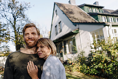 Smiling affectionate couple in garden of their home - p300m2205506 by Kniel Synnatzschke