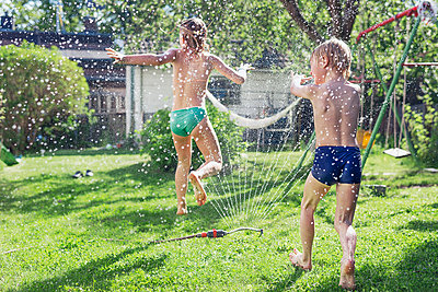 Boy and girl playing in garden - p312m993235f by Johan Willner