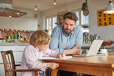 Father helping son with homework in home office - p429m1140121 by Stephen Lux