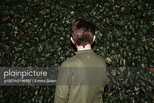 Rear view of teenage girl against green hedge - p1507m2196557 by Emma Grann