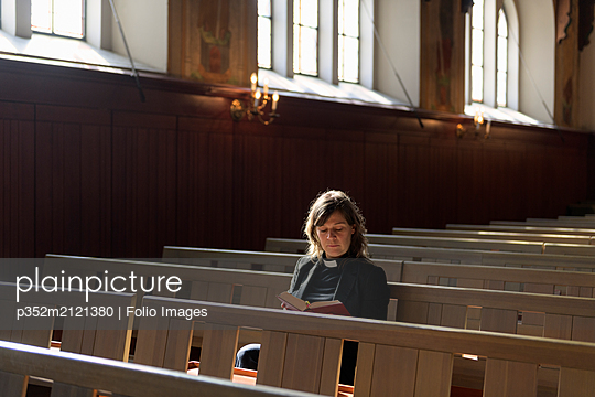 Priest reading bible on church pew - p352m2121380 by Folio Images