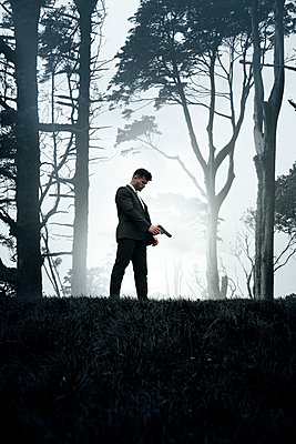 Man with Suit and Gun on Forest Hilltop - p1248m2134697 by miguel sobreira
