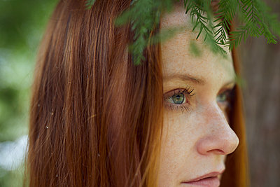 Portrait of red-haired woman in a park, close-up - p1491m2176089 by Jessica Prautzsch