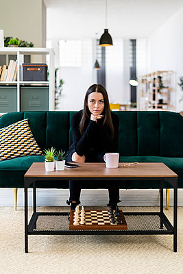 Confident young woman sitting on sofa in living room at loft apartment - p300m2225677 by Giorgio Fochesato