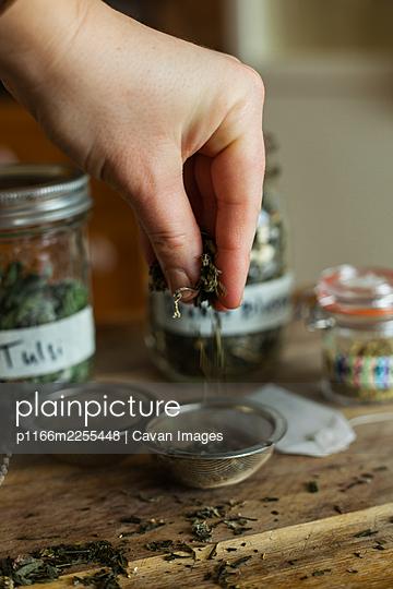 Flat lay of loose leaf herbal tea ingredients on a wooden background - p1166m2255448 by Cavan Images