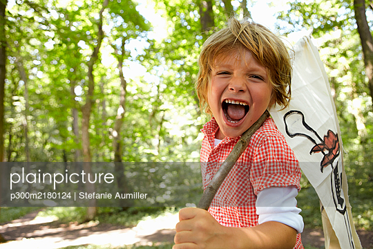 Portrait of screaming boy carrying pirate flag in forest - p300m2180124 by Stefanie Aumiller