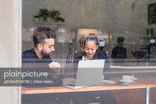 Couple in cafe using laptop - p312m2138750 by Viktor Holm
