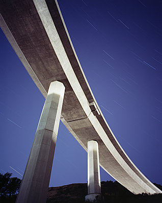 Low angle view of overpass against star trails at night - p1166m1194005 by Cavan Images