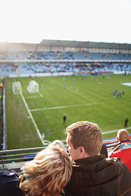 Rear view of couple watching game of soccer in stadium - p1185m1078012f by Adam Haglund