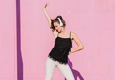 Happy young woman wearing headphones dancing in front of pink wall - p300m2059616 by Uwe Umstätter