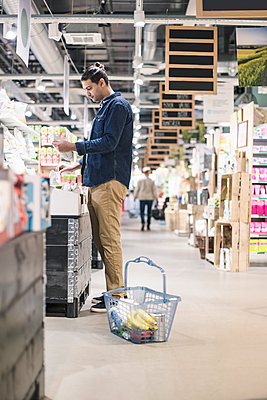 Side view of man buying groceries in supermarket - p426m1407366 by Kentaroo Tryman