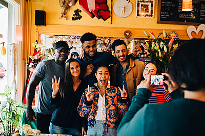 Young man photographing cheerful multi-ethnic friends standing at restaurant during brunch - p426m2046280 by Maskot