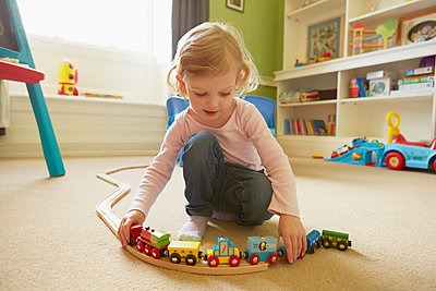 Female toddler playing with toy train on playroom floor - p429m1407994 by Emma Kim