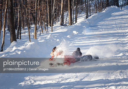 Young child sledding down a snowy hill in a wooded area on sunny day. - p1166m2255812 by Cavan Images