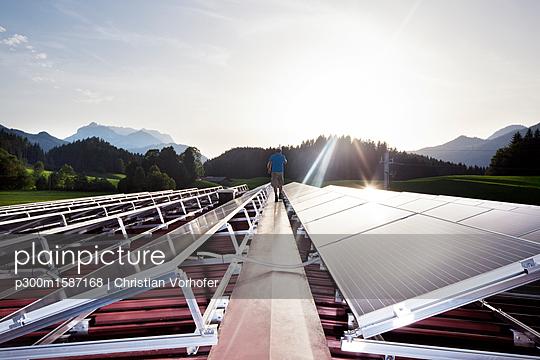 Austria, Tyrol, Koessen, back view of worker walking on solar plant in the evening - p300m1587168 von Christian Vorhofer