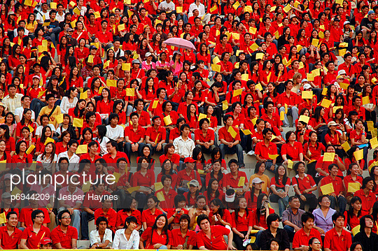 Asian Crowd Wearing Red Shirts and Holding Yellow Flags