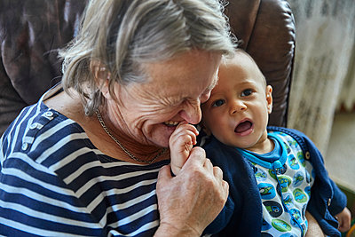 Grandmother and grandson on the sofa, portrait - p1146m2187818 by Stephanie Uhlenbrock
