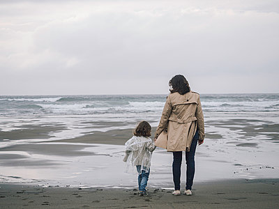 Mother and daughter holding hands in front of the sea - p1522m2100587 by Almag