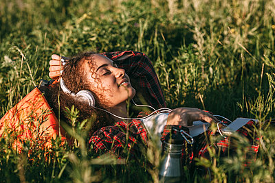 Teenage girl with backpack lying on a meadow listening music with headphones and cell phone - p300m1505493 by Vasily Pindyurin