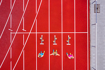 Germany, Baden Wurttemberg, Winterbach, Aerial view of three female sprinters standing at track starting block - p300m2156701 by Stefan Schurr