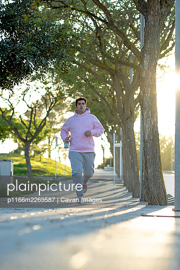 Fat man running down the sidewalk in a park with sunset light behind - p1166m2269587 by Cavan Images