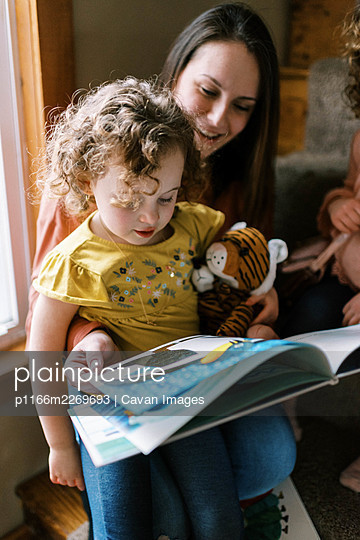 A child sitting on her mothers lap reading a book together on stairs - p1166m2269693 by Cavan Images