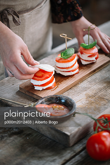 Woman preparing Caprese Salad, partial view - p300m2012403 by Alberto Bogo