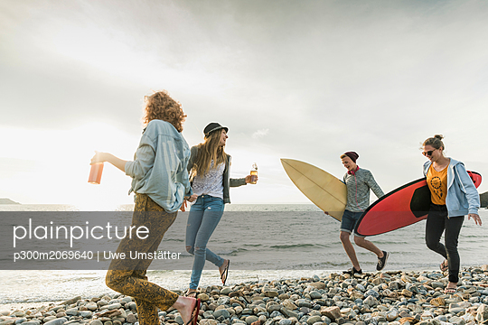 Happy friends with surfboards walking on stony beach - p300m2069640 by Uwe Umstätter