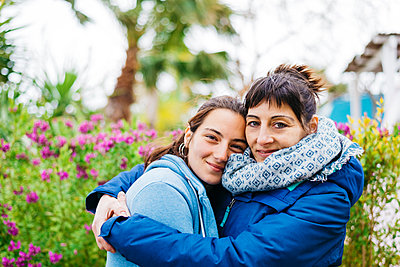 Portrait of mother hugging daughter while looking camera outdoors - p1166m2094330 by Cavan Images