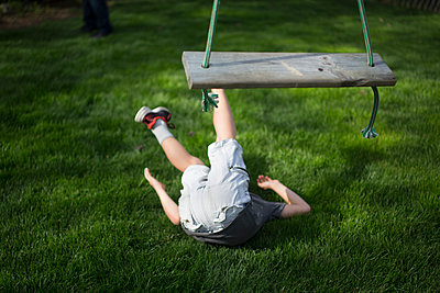 A child lays on the ground after falling from a wooden swing - p1166m2130163 by Cavan Images
