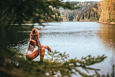 Frau posiert vor ruhigem Bergsee - p1455m2204902 von Ingmar Wein