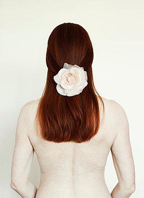 Rückenansicht einer Frau mit Blume im Haar - p1574m2191466 von manuela deigert