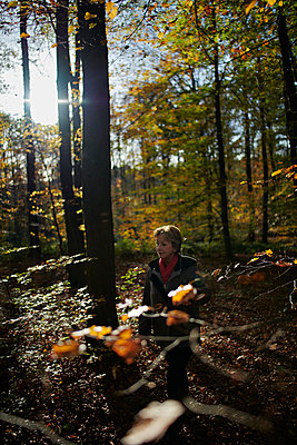 Woman walking throuth the forest - p227m1503293 by Uwe Nölke