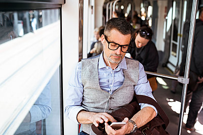 Businessman with smartphone and earphones travelling in tram - p300m1469647 by HalfPoint