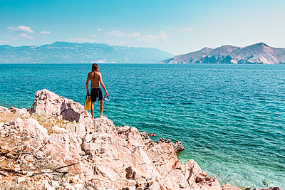 Croatia, Krk, man standing on rock formation and looking at sea - p300m2199630 by Valentin Weinhäupl