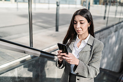 Businesswoman using smart phone while standing on escalator in city - p300m2265895 by COROIMAGE